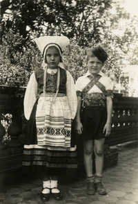 Girl and boy in costume on porch of Main Library