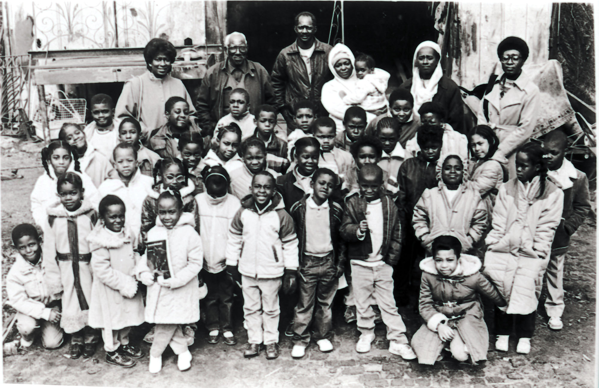 Philip Simmons and a group of children in front of his workshop.