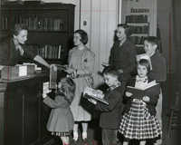 Family checking out books at the Circulation desk, Main Library