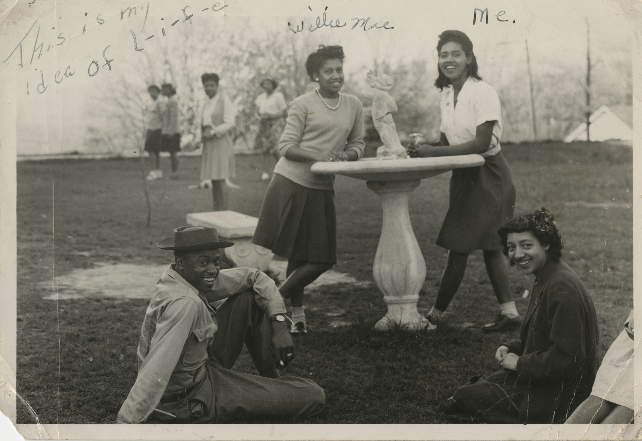 Four People Next to Bird Bath