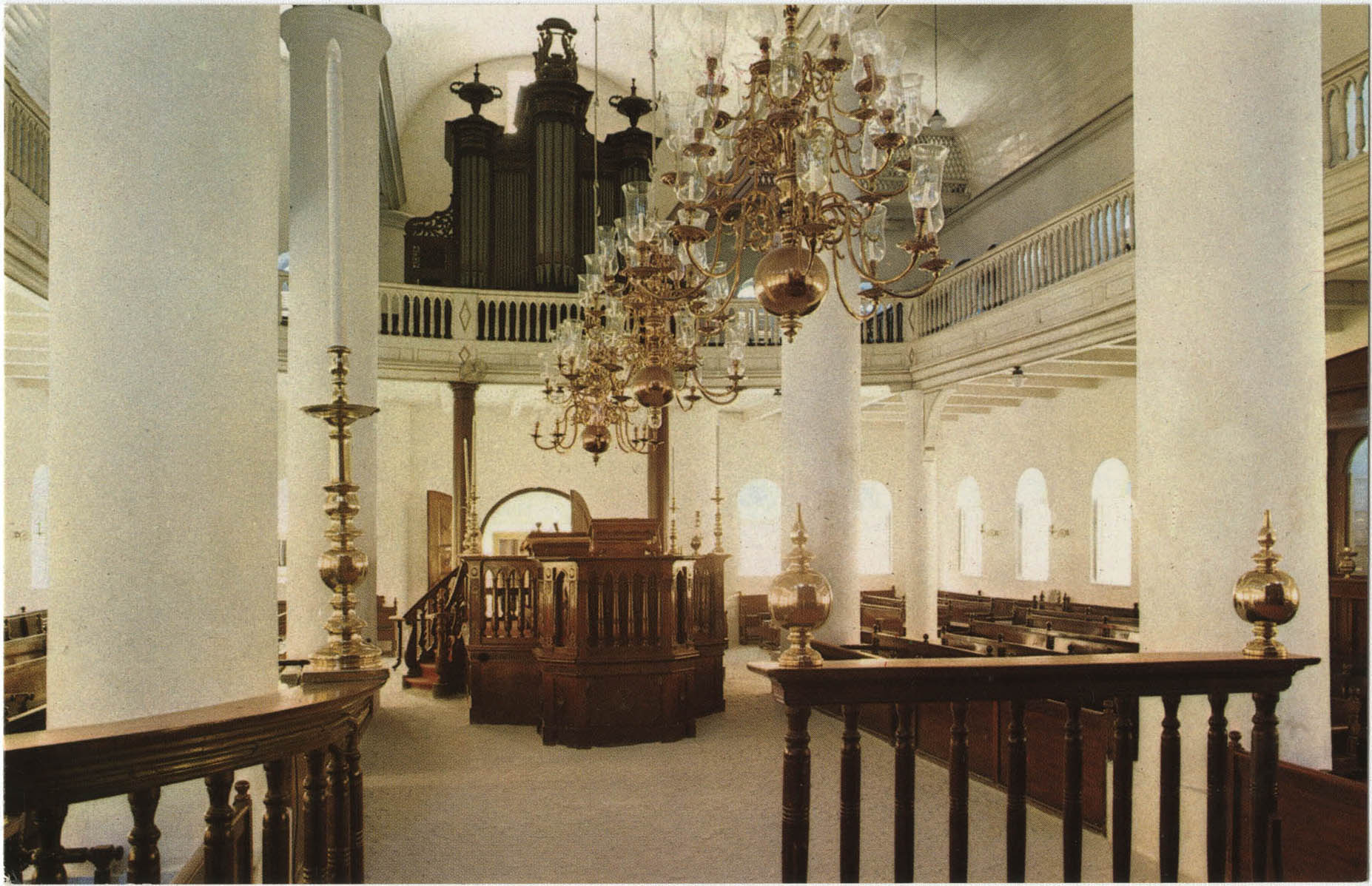 Interior of Mikve Israel-Emanuel Synagogue, dedicated in 1732, oldest in continuous use in Western Hemisphere. View is towards main entrance, showing Tebah (reading platform) and beautiful old brass chandeliers over sandcovered floor flanked by mahogany wooden benches.