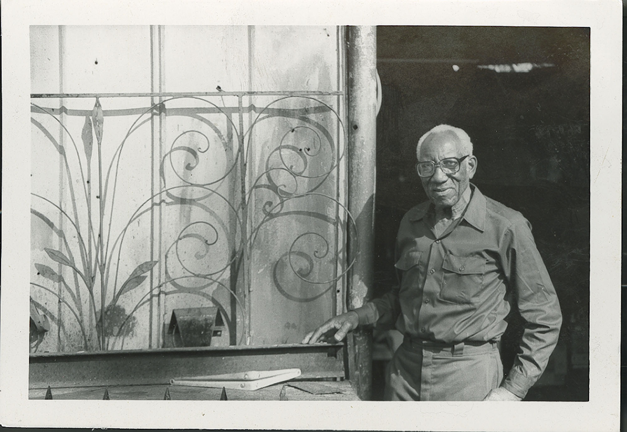 Photograph Philip Simmons standing next to railing outside his workshop.