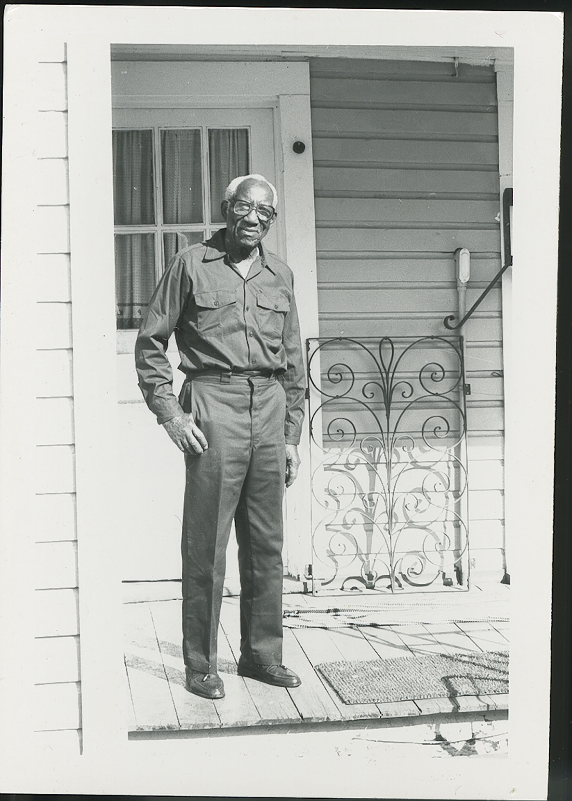 Photograph Philip Simmons standing next to window grate on his porch.