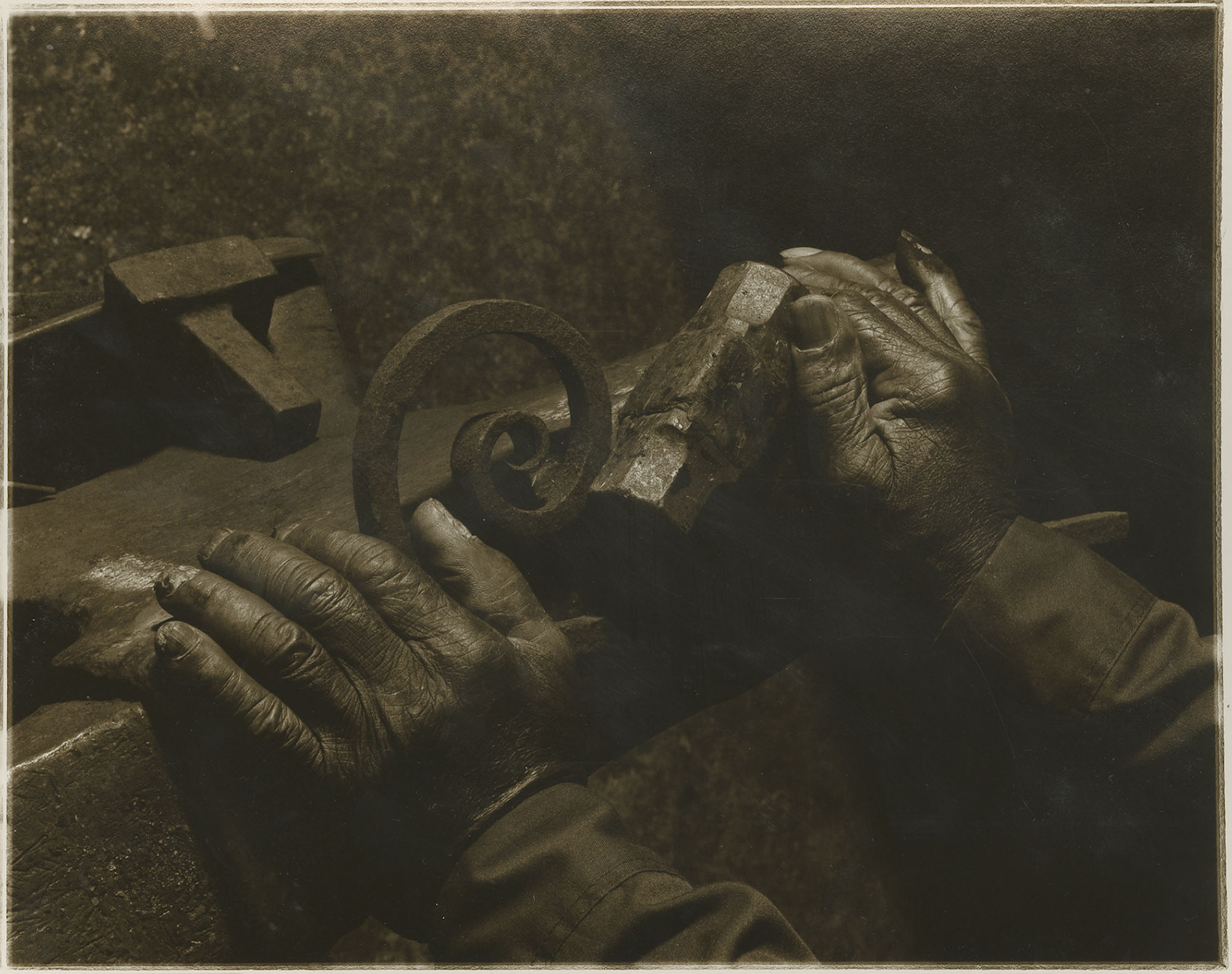Photograph of Philip Simmons hands holding hammer and scrolled piece of iron.
