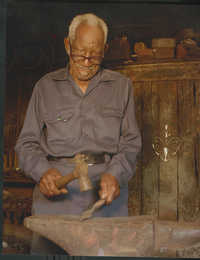 Photograph of Philip Simmons working in his shop.