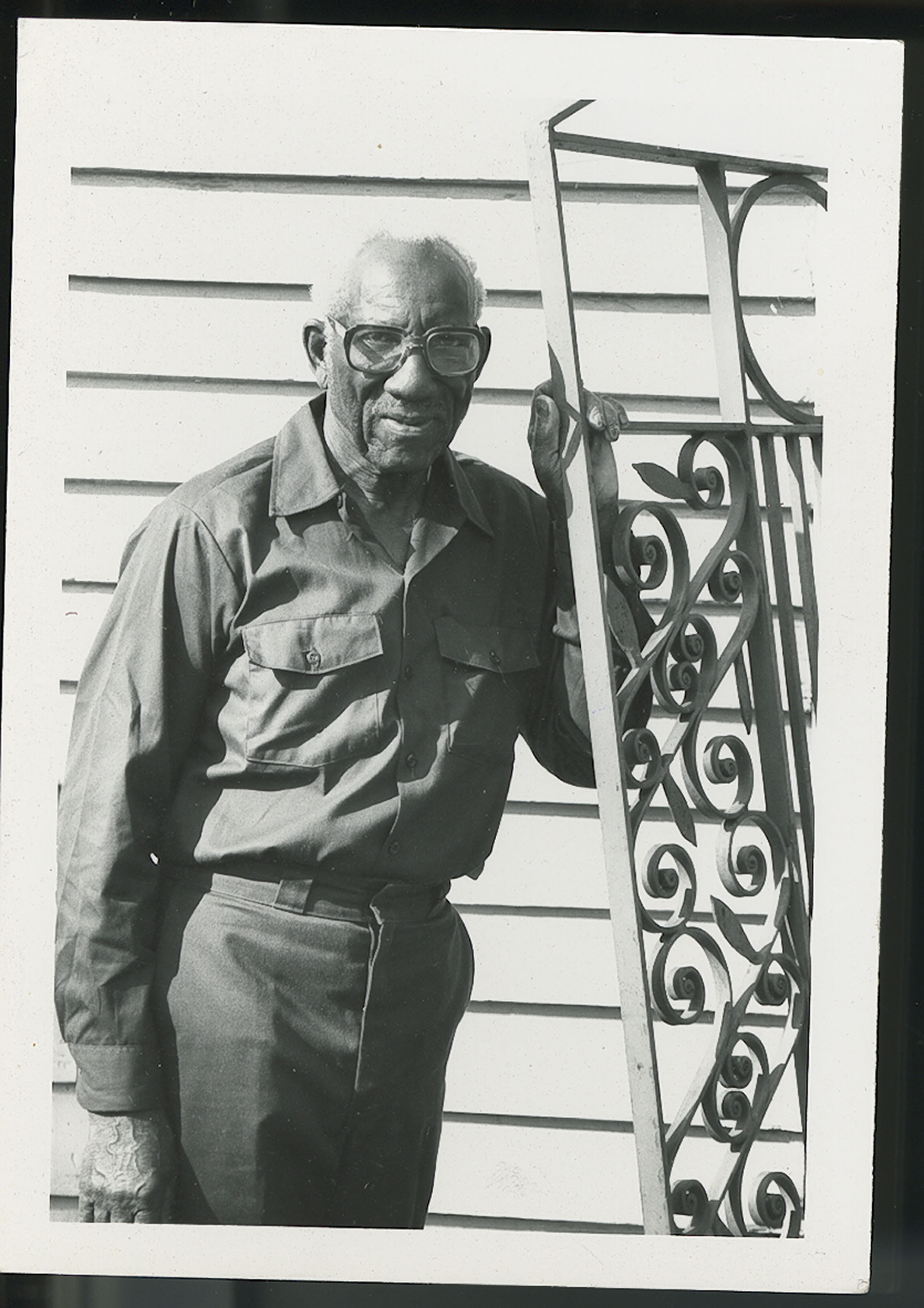 Photograph Philip Simmons standing next to a gate.