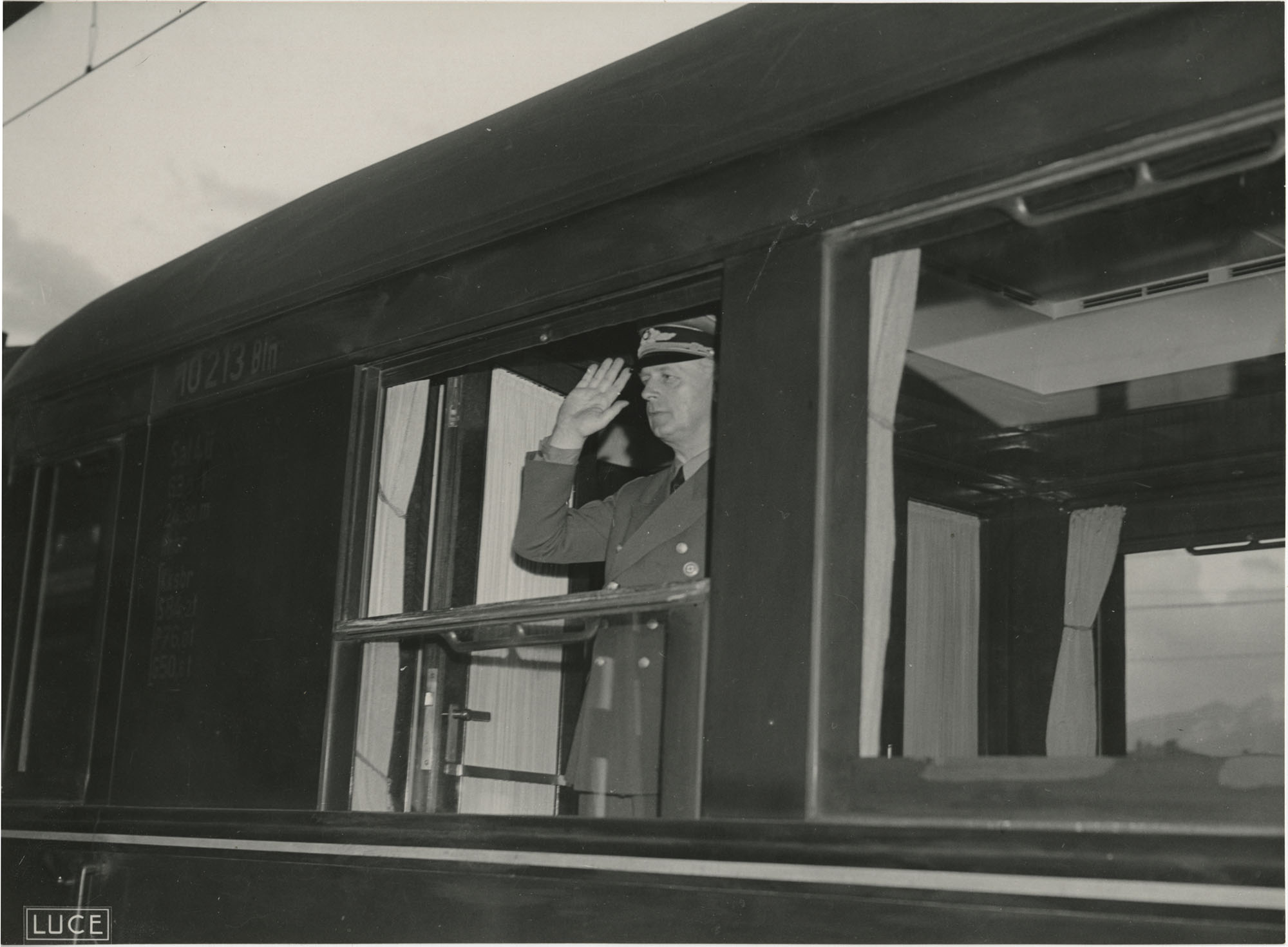 A military official saluting from the window of a train