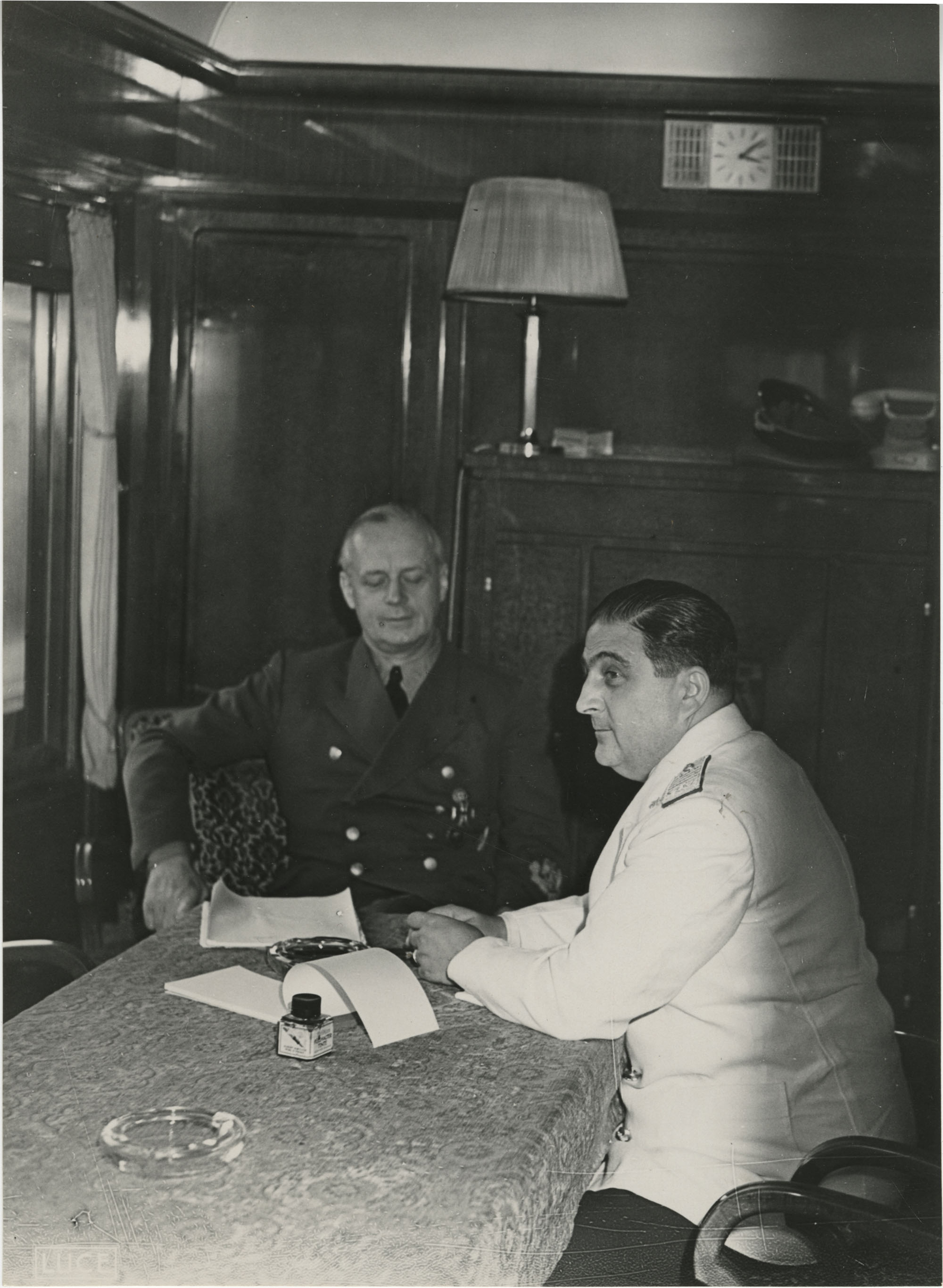 Military officials conversing on a train, Photograph 1