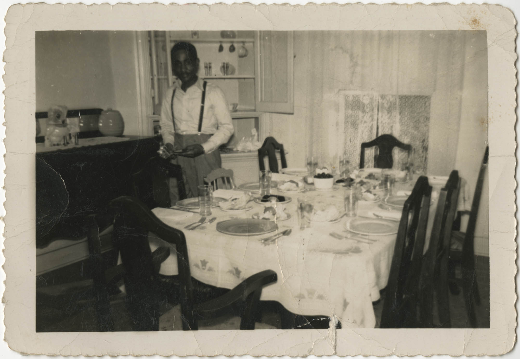 Photograph of a Man Setting a Dining Room Table