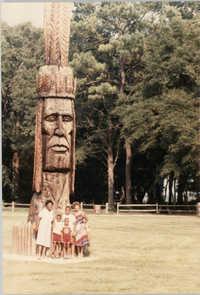 Photograph of a Family Standing Beside a Wooden Sculpture