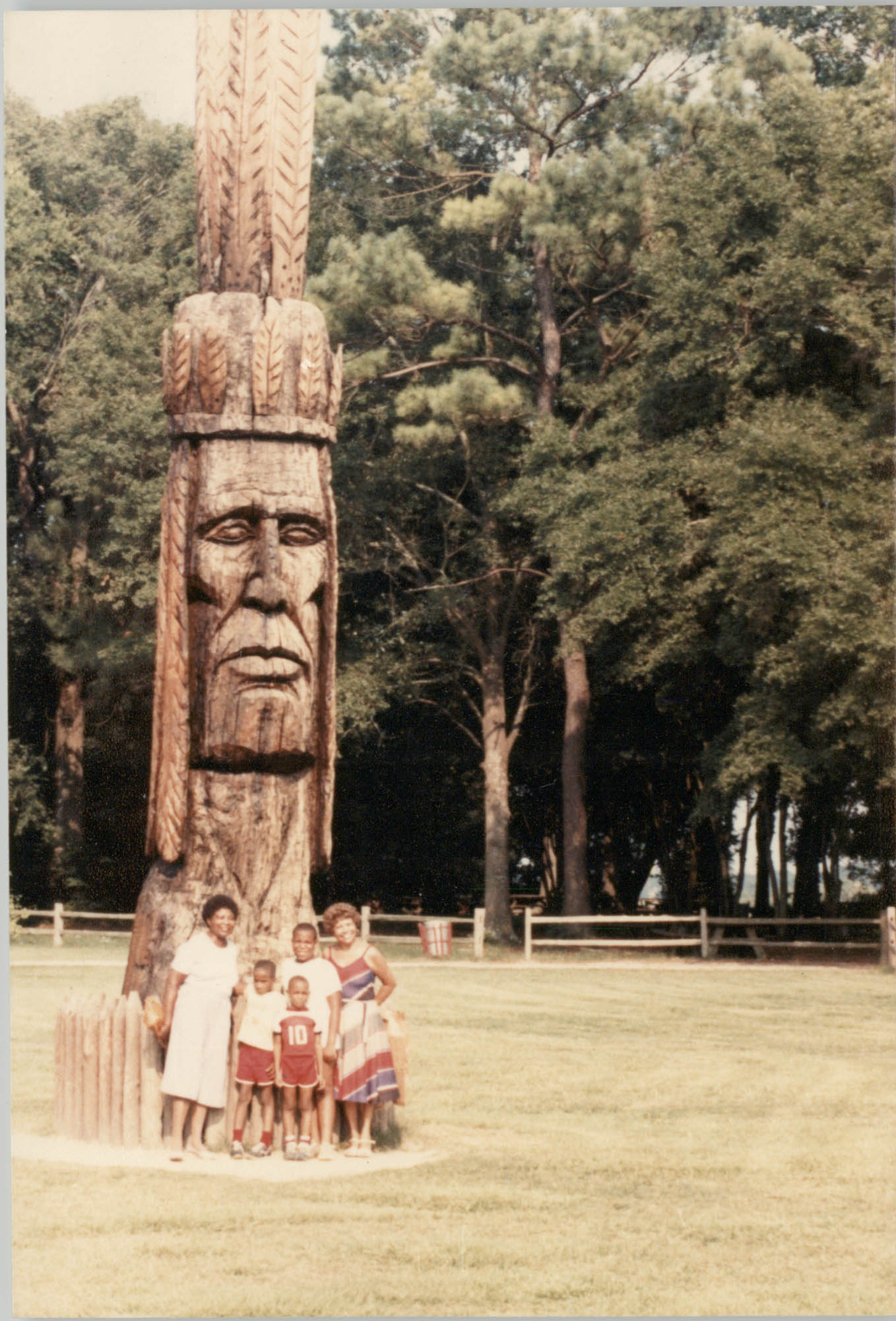 Photograph of a Family Standing Beside a Wooden Sculpture