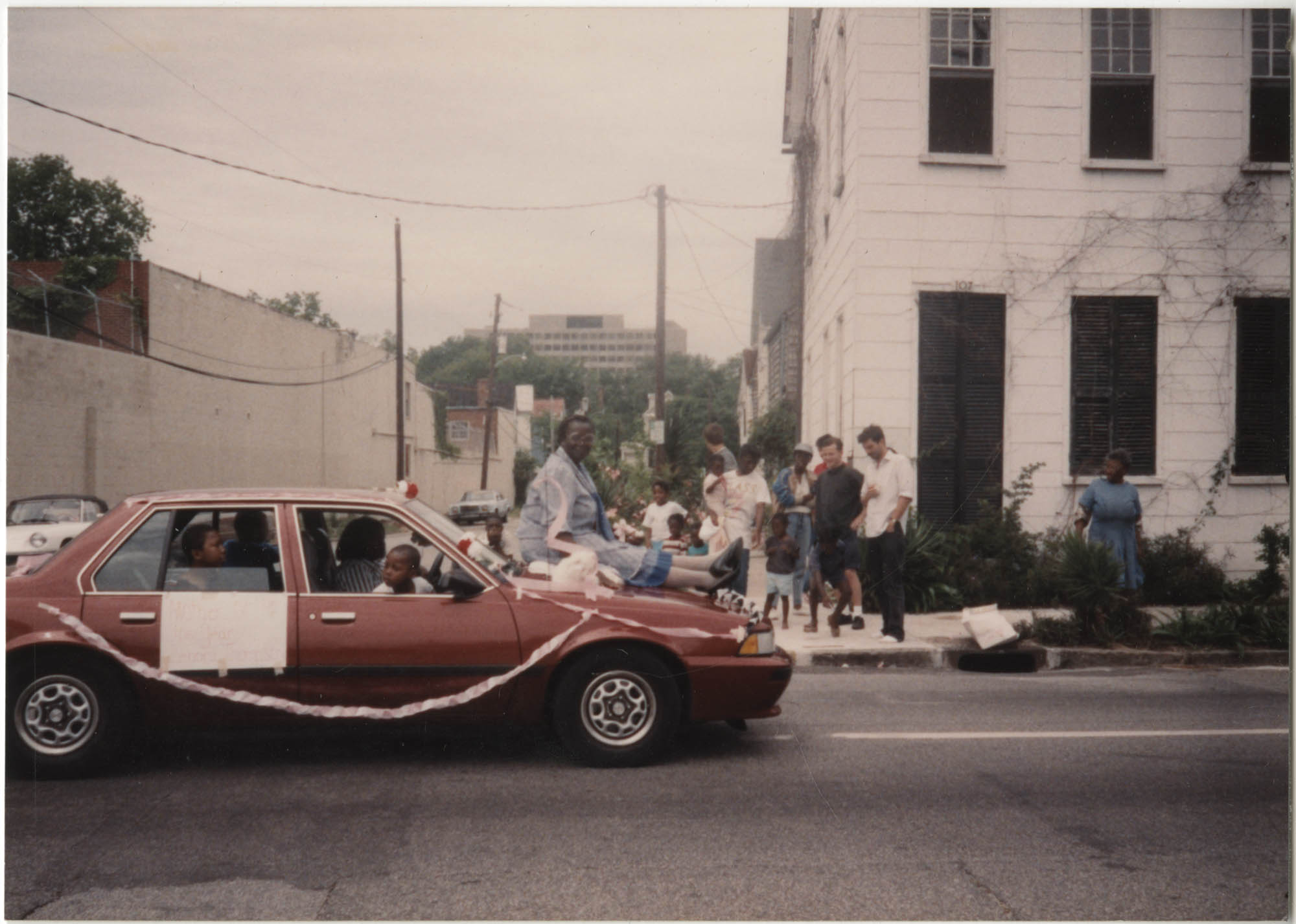 Photograph of a Woman Sitting on the Hood of a Car