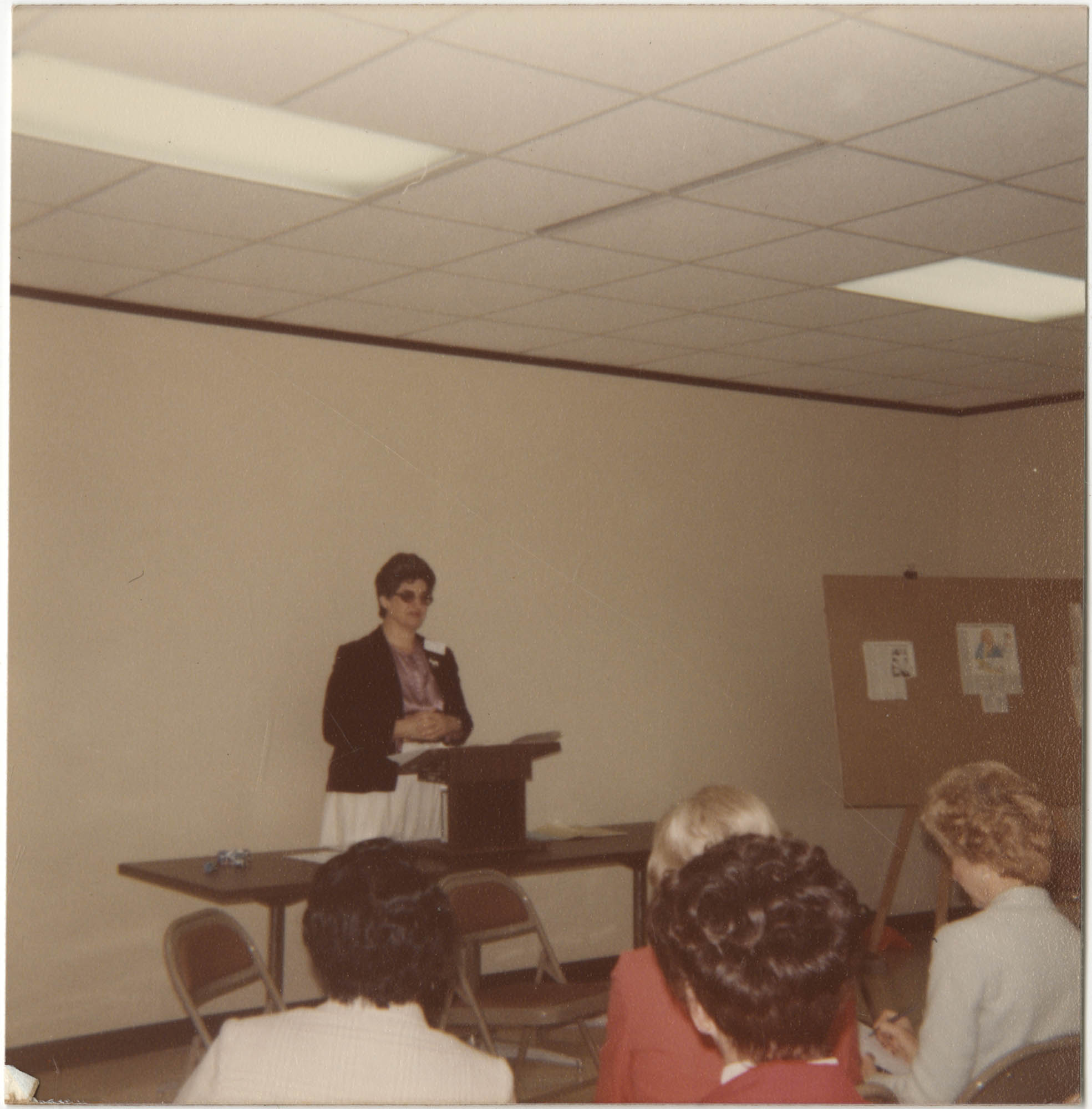 Photograph of a Women Speaking in Front of a Group