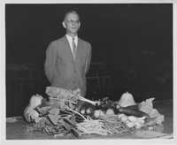 Man Standing Behind a Sampling of Vegetables