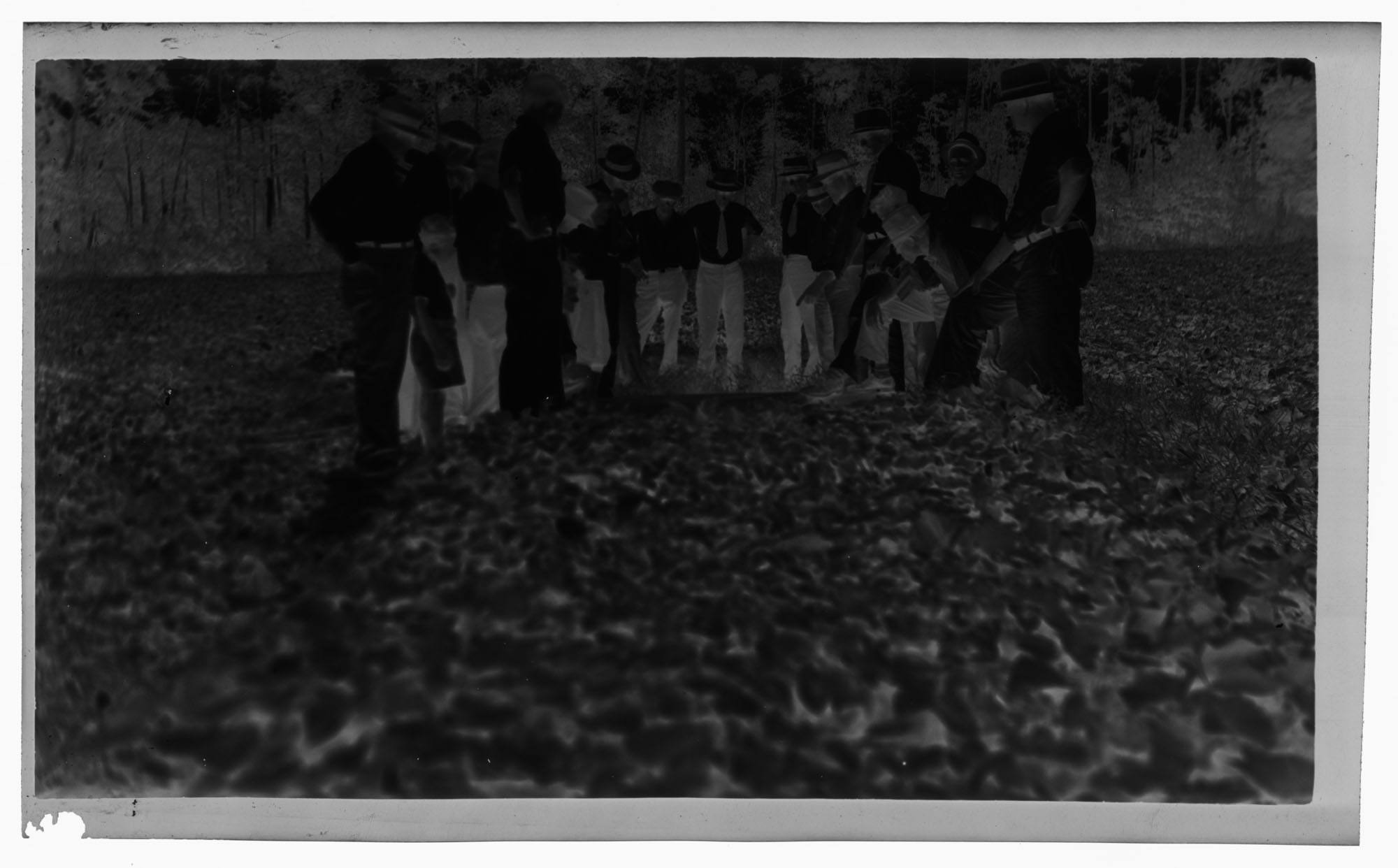 Negative of Men Gathering Over a Field