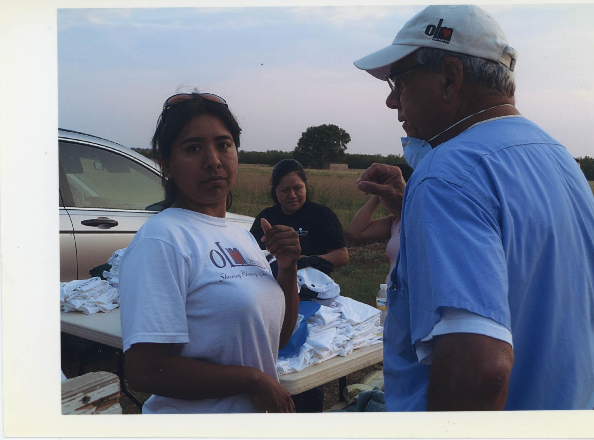 Fotografía de Alma López junto al doctor John Howard visitando trabajadores agrícolas migrantes  /  Photograph of Alma López and Doctor John Howard Visiting Seasonal Migrant Workers