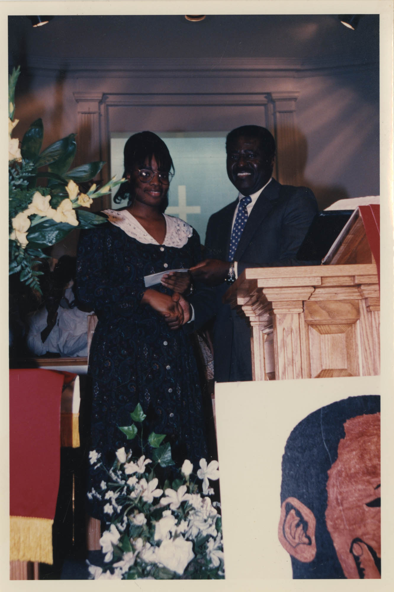 Photograph of Two People Behind a Podium