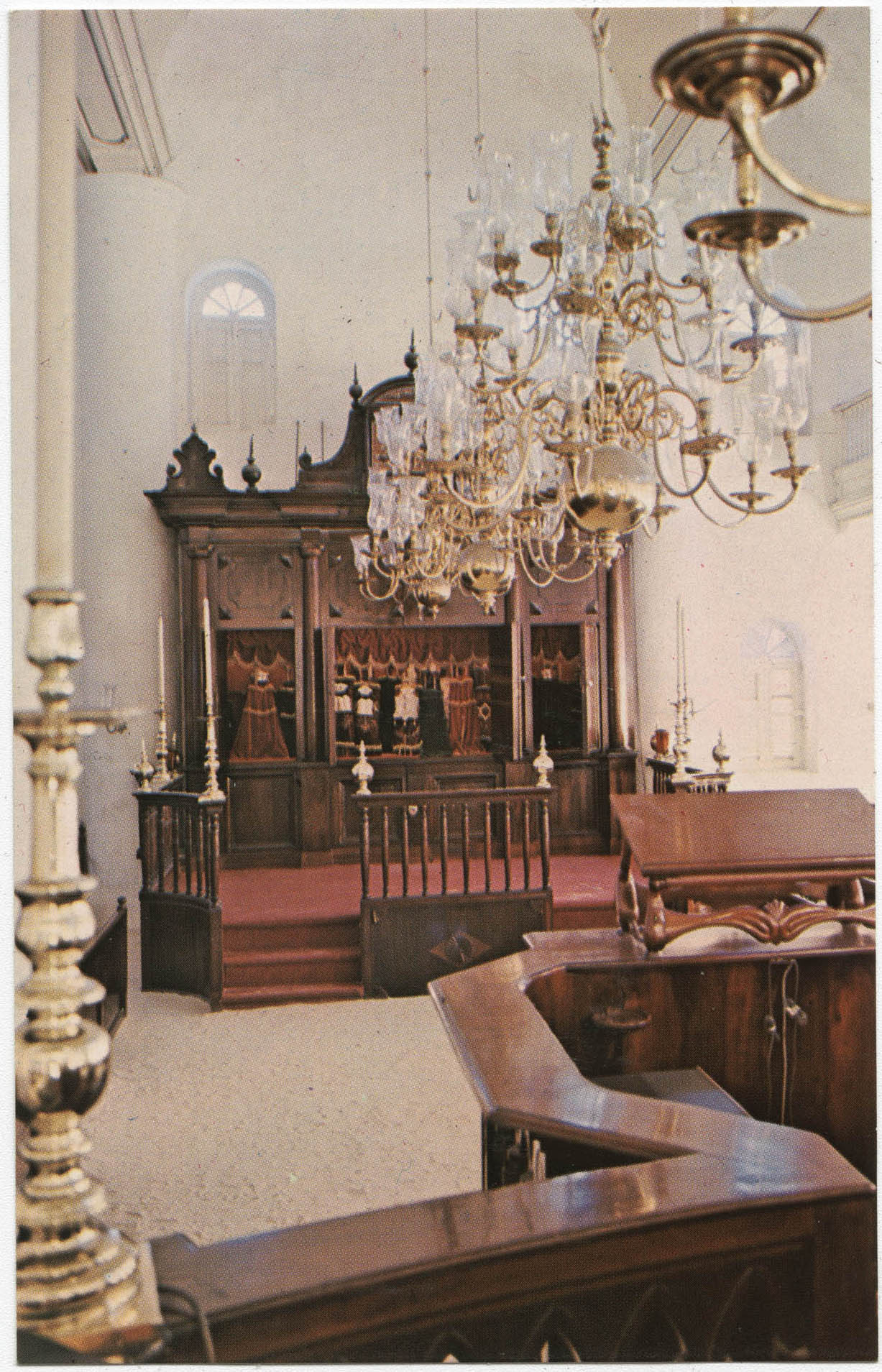 View of interior of Mikve Israel-Emanuel Synagogue looking towards Hekhal containing 18 scrolls and showing old brass chandeliers and sandcovered floor flanked by wooden benches.