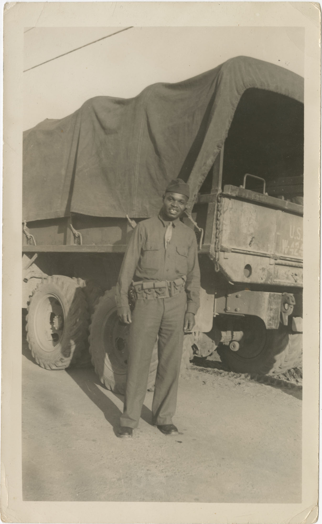 Photo of an African American Man Posing Next to a Military Truck
