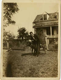 Herbert U. Seabrook, Sr. standing in yard beside a cow