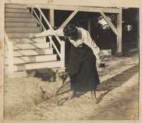 Woman playing with dogs in front of Halls Island house