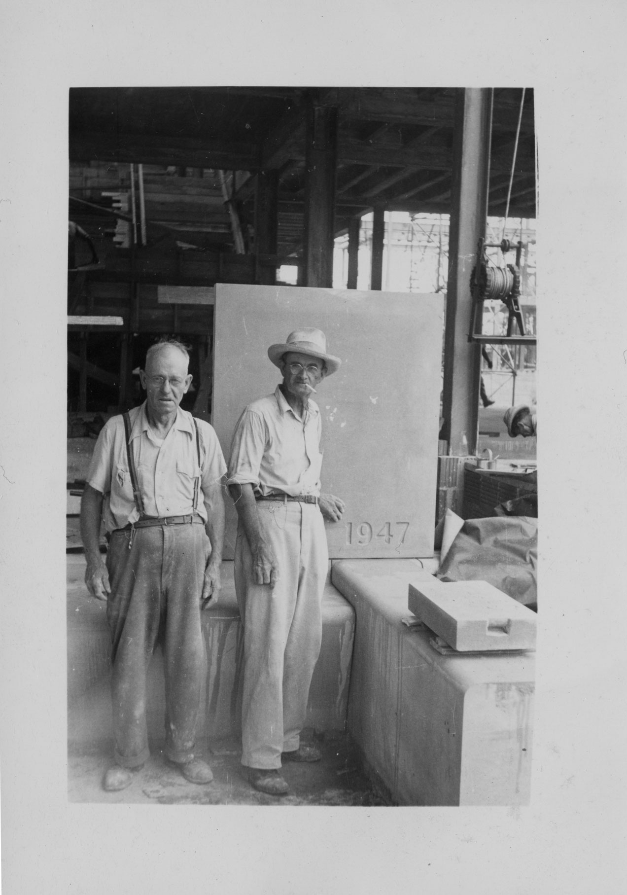 Two workmen by the 1947 Cornerstone for the Naval Hospital