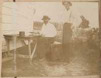 Leonard Donner at table outside; unidentified man beside him