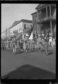 Girl Scouts marching in the Armistice Day parade in front of the John Mark Verdier House