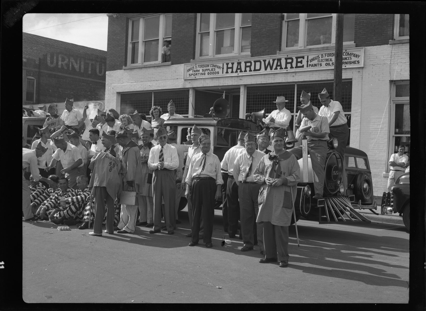 Group of participants in the 40 and 8 parade in front of Fordham Hardware
