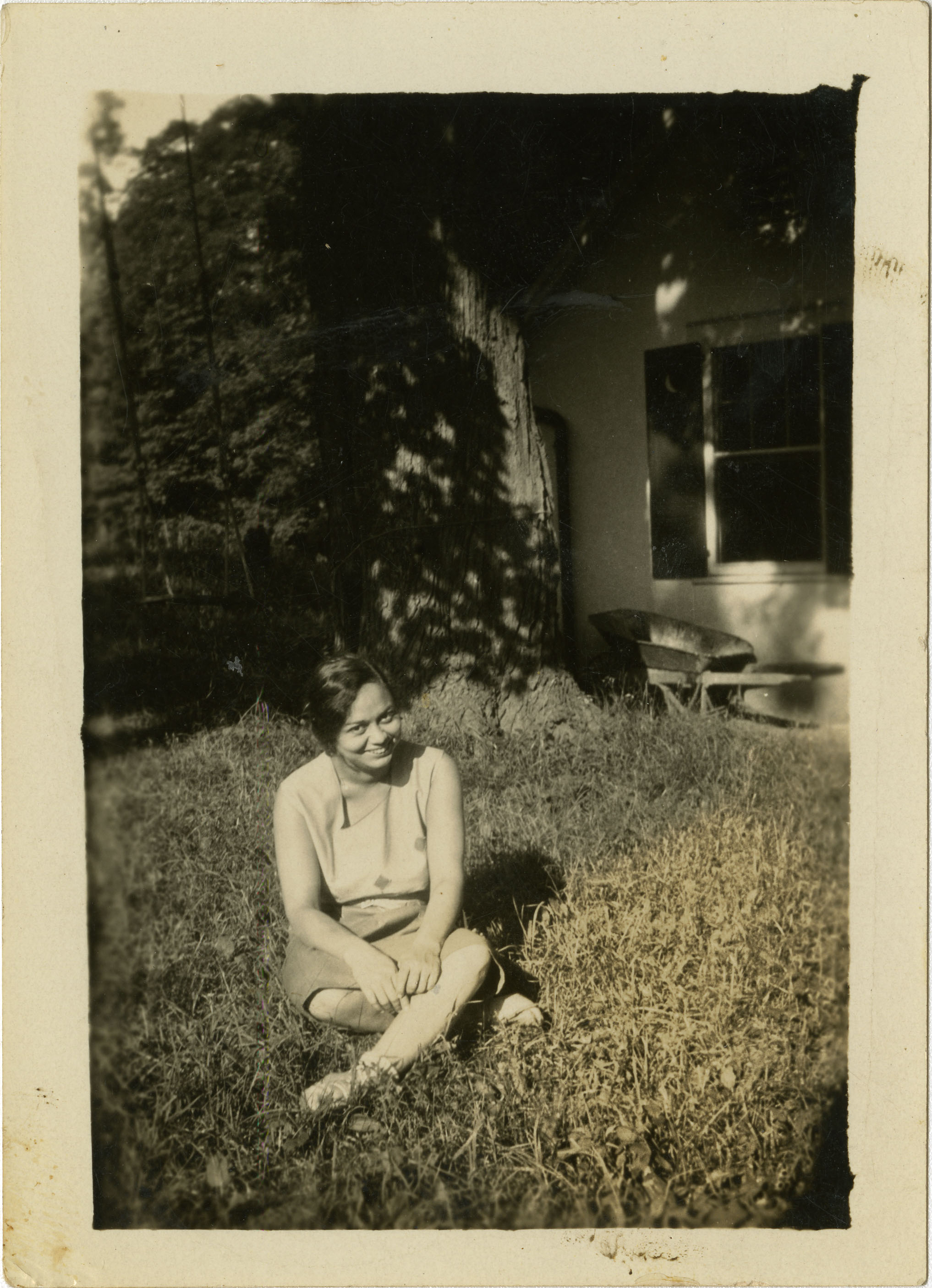 Woman sitting on grass in yard