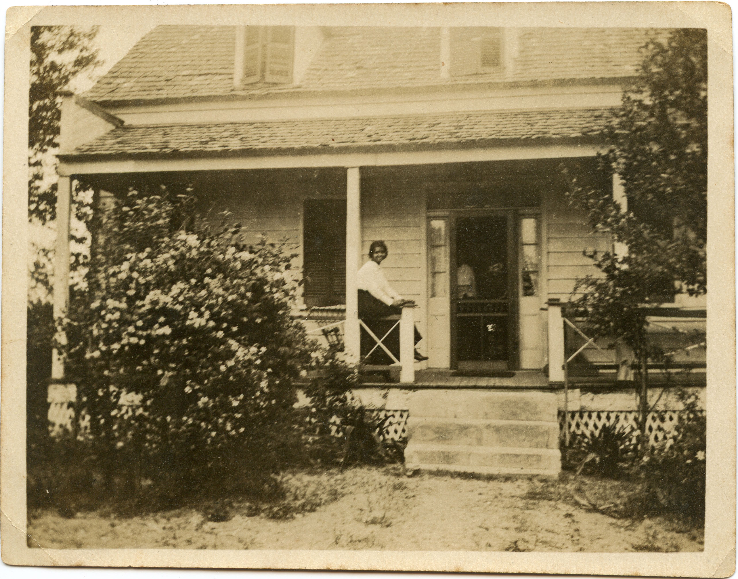 Miriam DeCosta Seabrook seated on porch railing