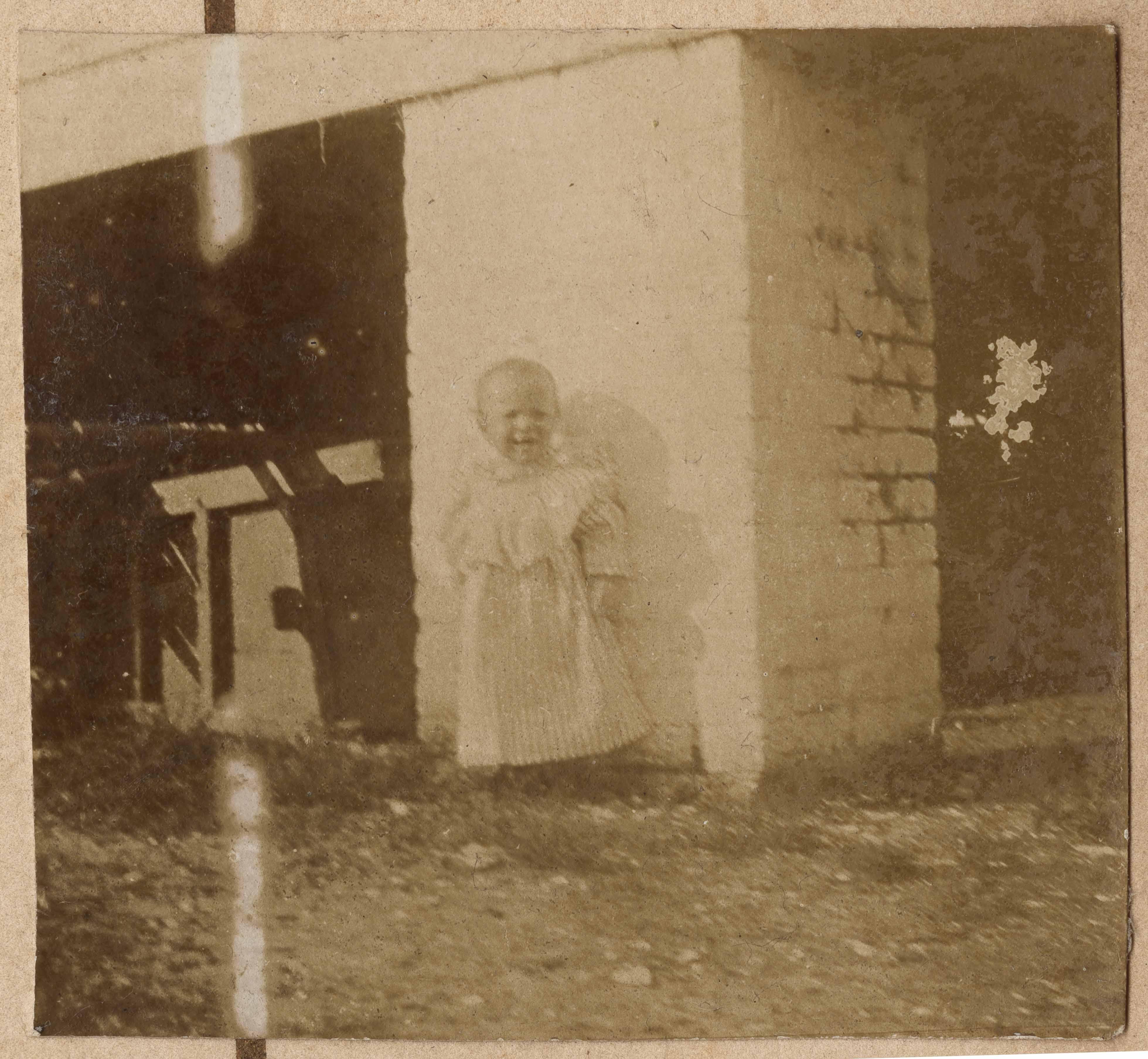 Unidentified child by white brick pier