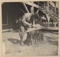 Man carving model boat keel on tree stump