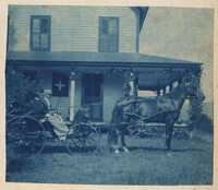 Man and woman in horse buggy in front of 2 story house