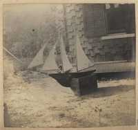 Model boat with sails ashore in front of Main house