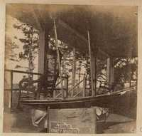 Model boat with mast near rocking chairs