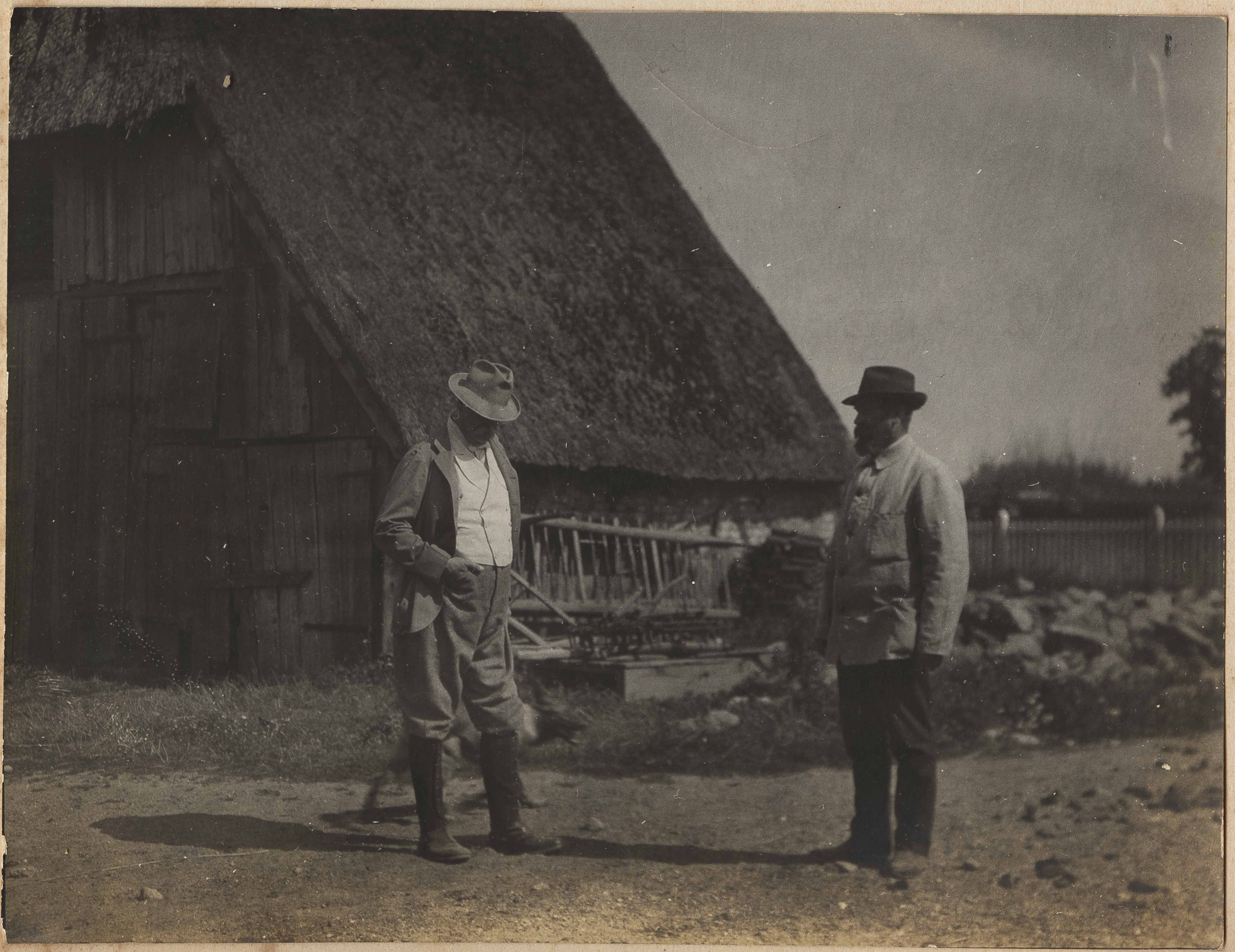 Two men in front of hay wagon in Altona