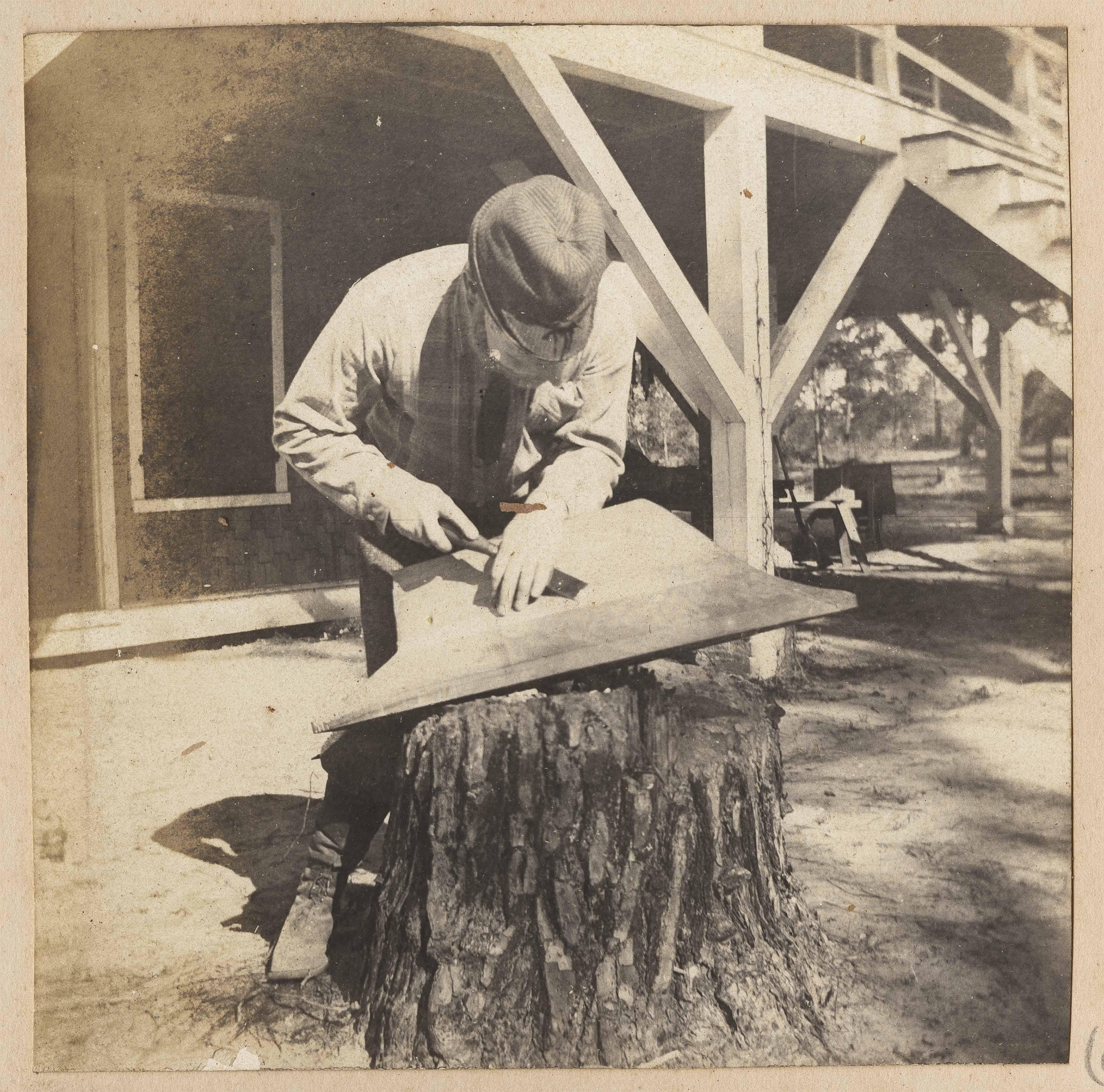 Man carving model boat keel