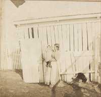 Woman holding child near shed