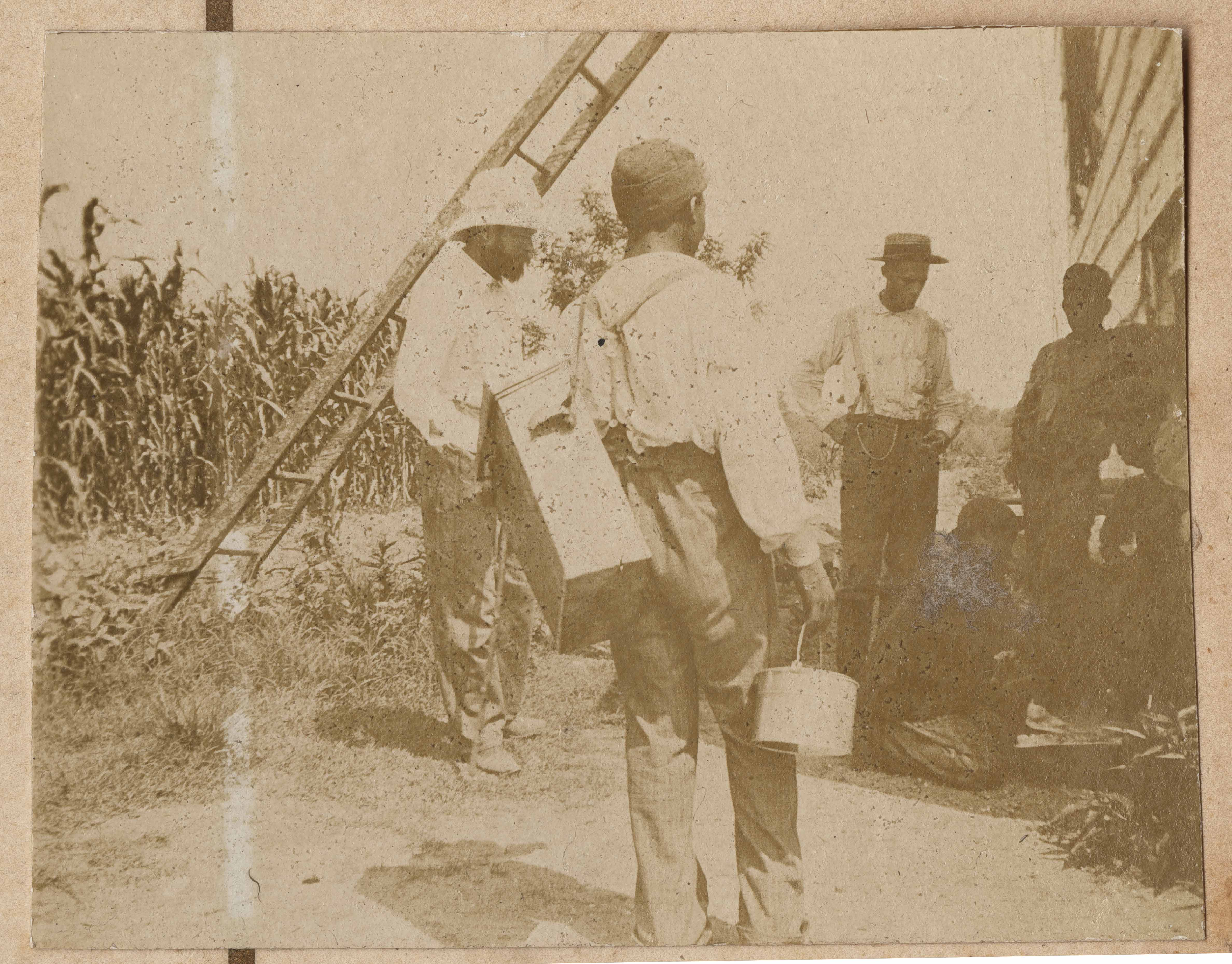 Conrad Donner with group of workers near corn field and barn