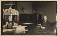 Christopher Donner reading beside piano
