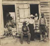 Pauline Donner with group of African Americans outside cabin