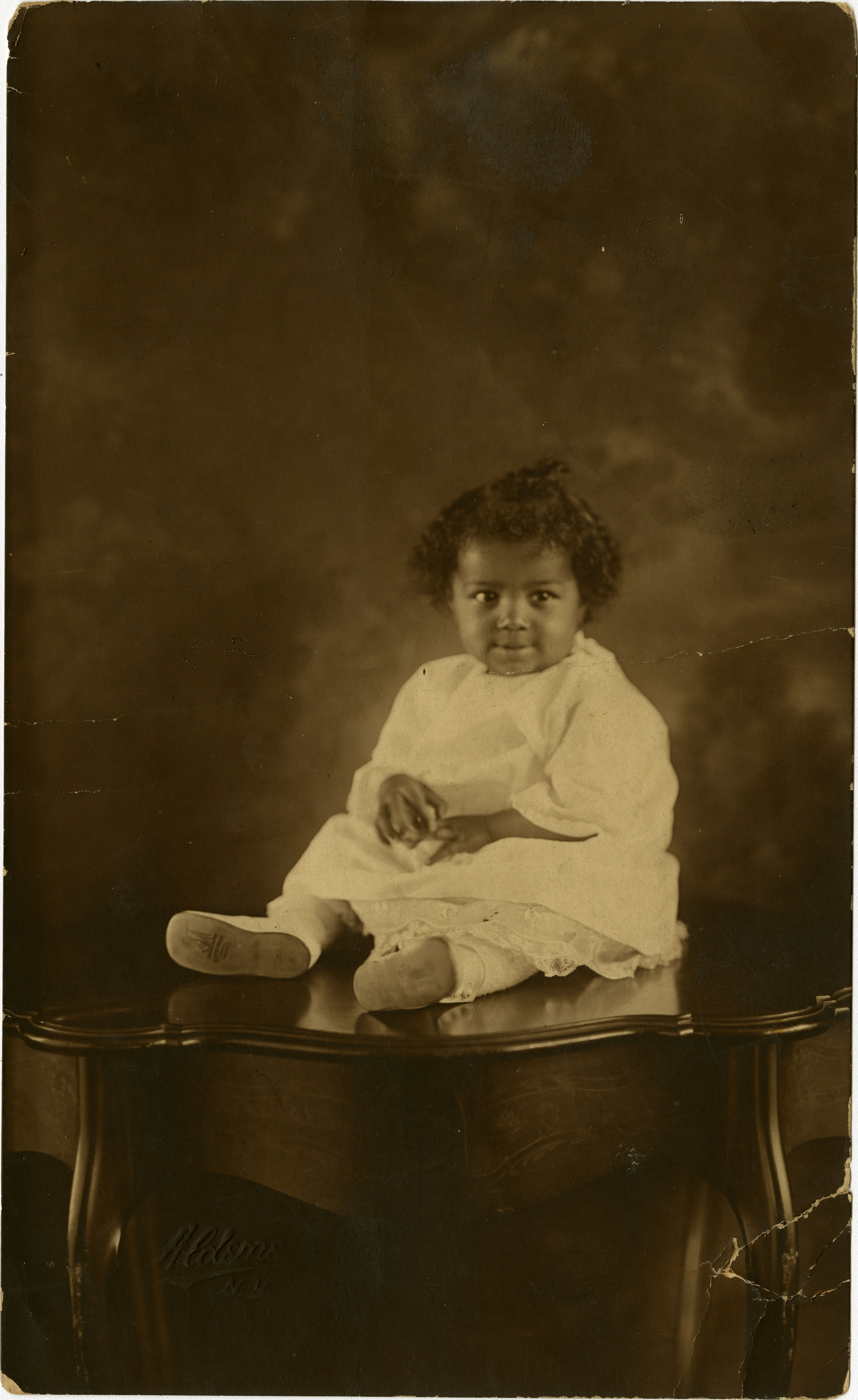 Formal portraint of infant sitting on table