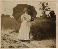 Portrait of woman with opened umbrella and basket