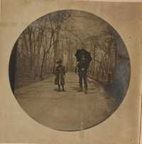 Child and man with umbrella in wooded area.