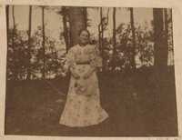 Unidentified young woman posing by tree