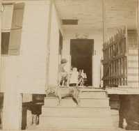 Man, child, and three dogs on porch