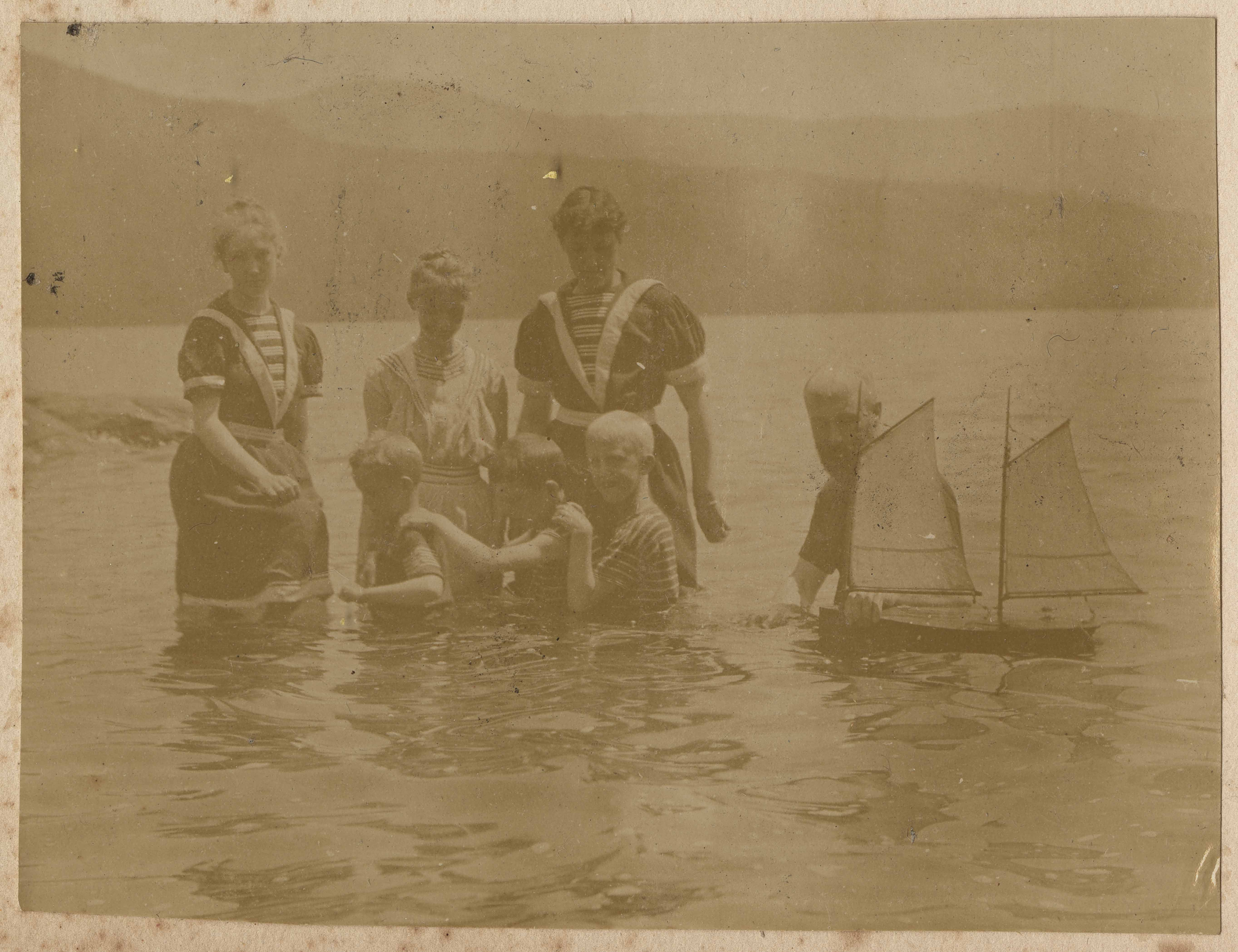Children in swimsuits with model boat