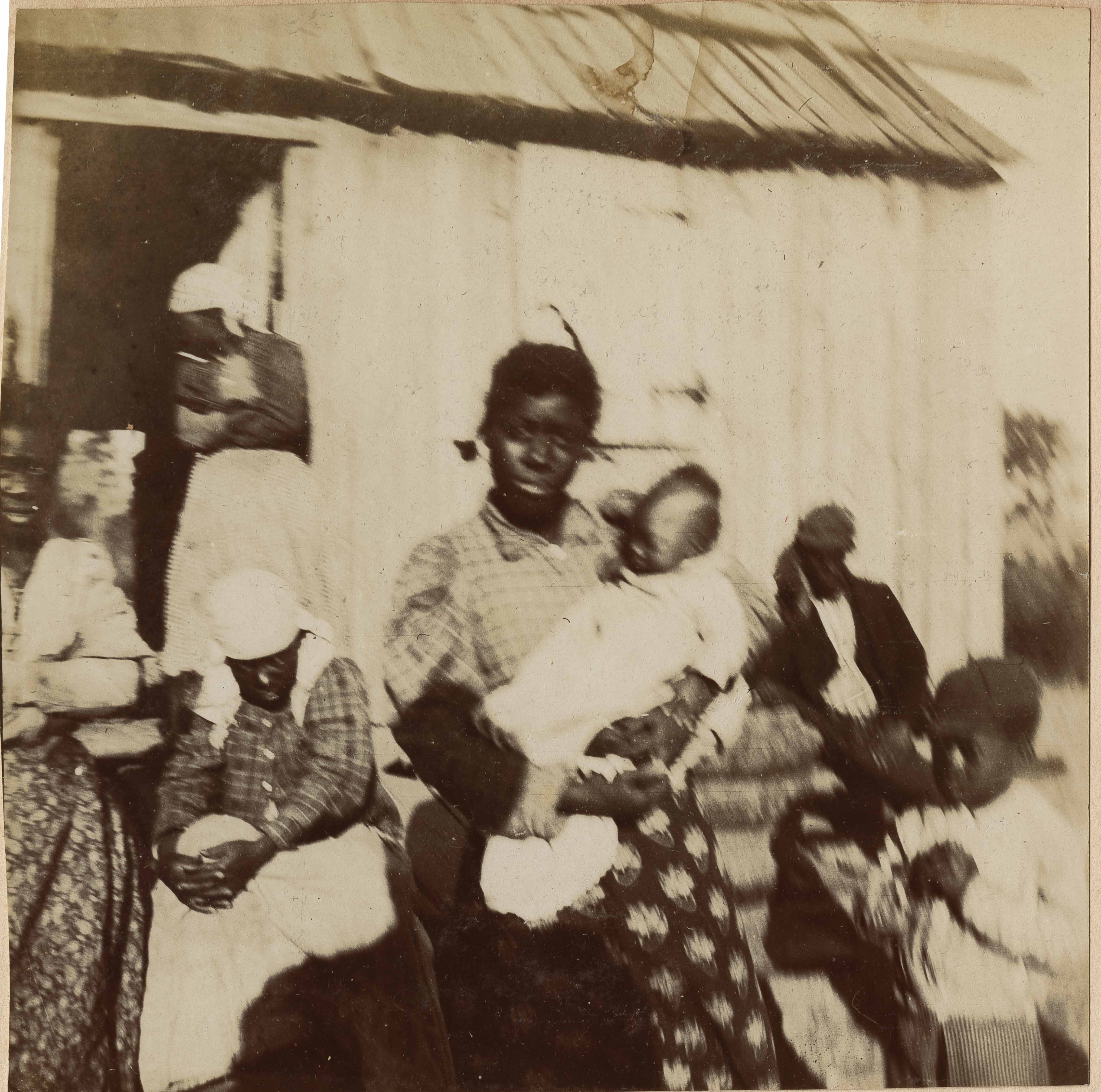 Girl holding baby surrounded by children and women in head scarves