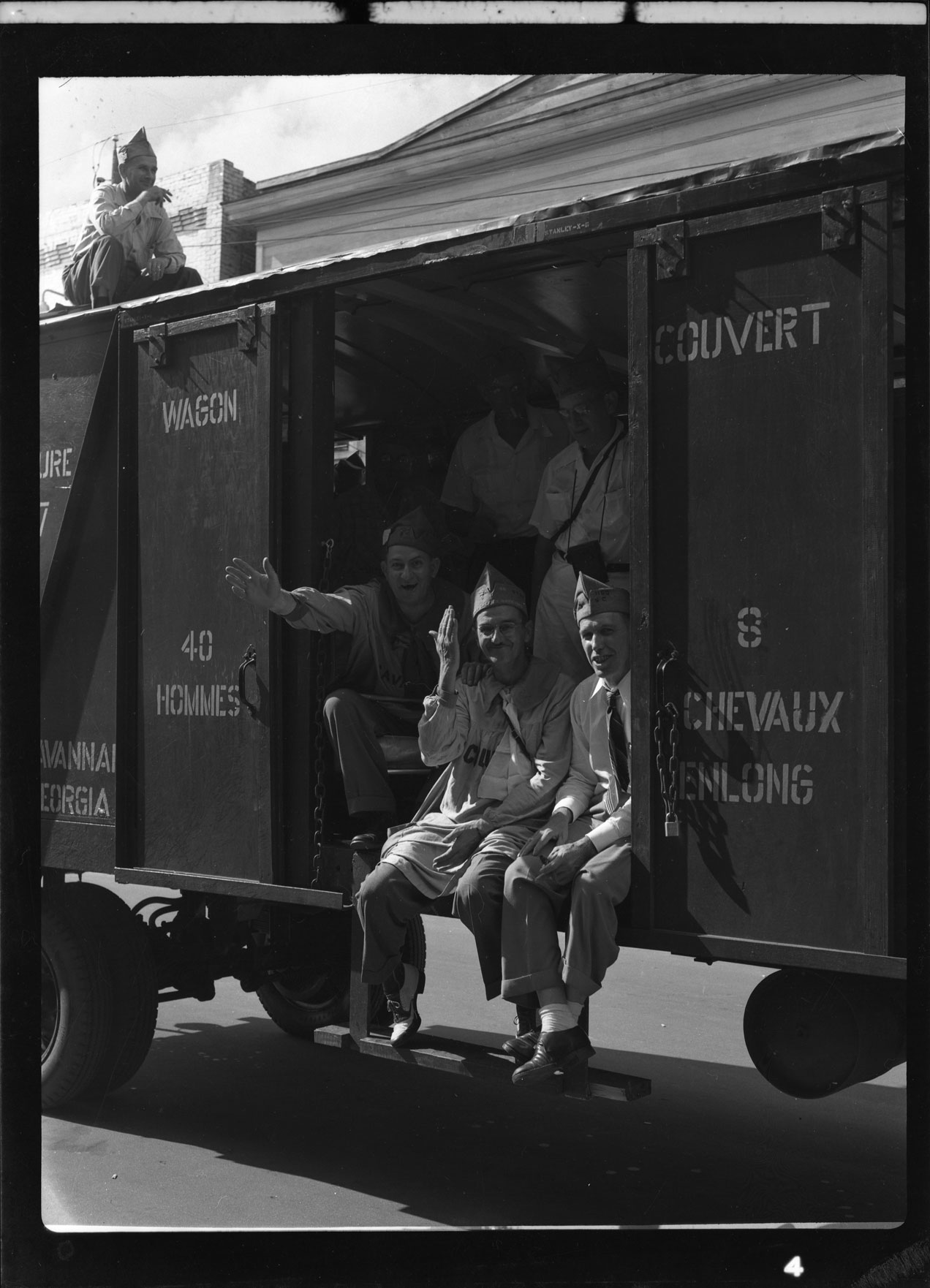 Men waving from the train boxcar in the 40 and 8 parade